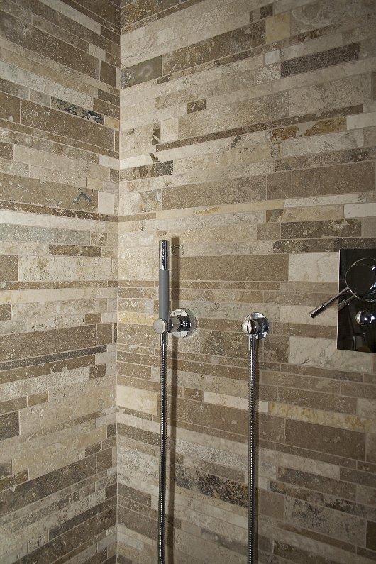 doccia con rivestimenti in mosaico di travertino